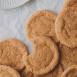 Overhead shot of snickerdoodle cookies on white parchment paper. One cookie has a bite out of it.