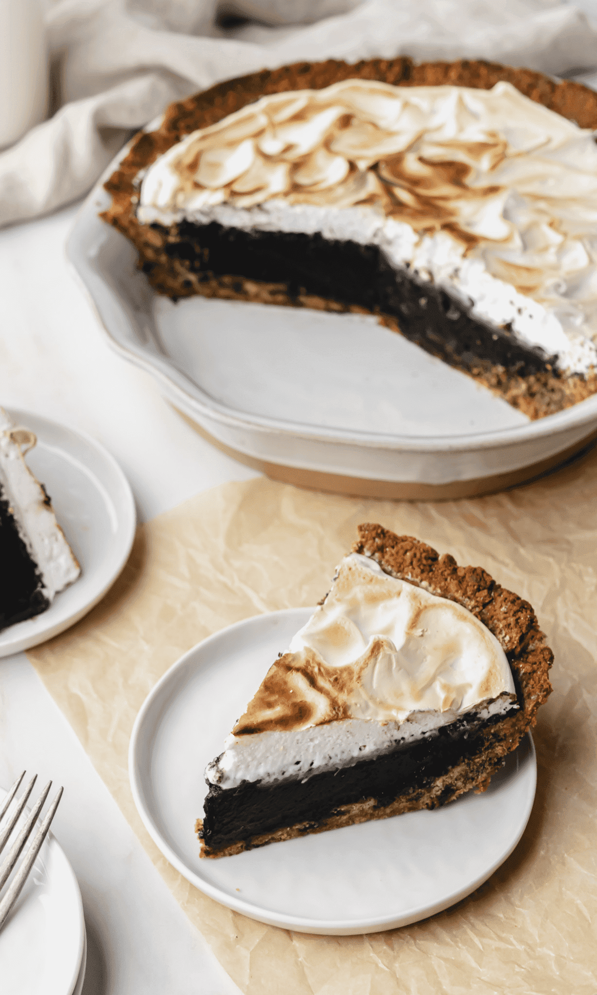 A piece of S'mores Fudge Pie on a small white plate with remaining pie in pie dish in background.
