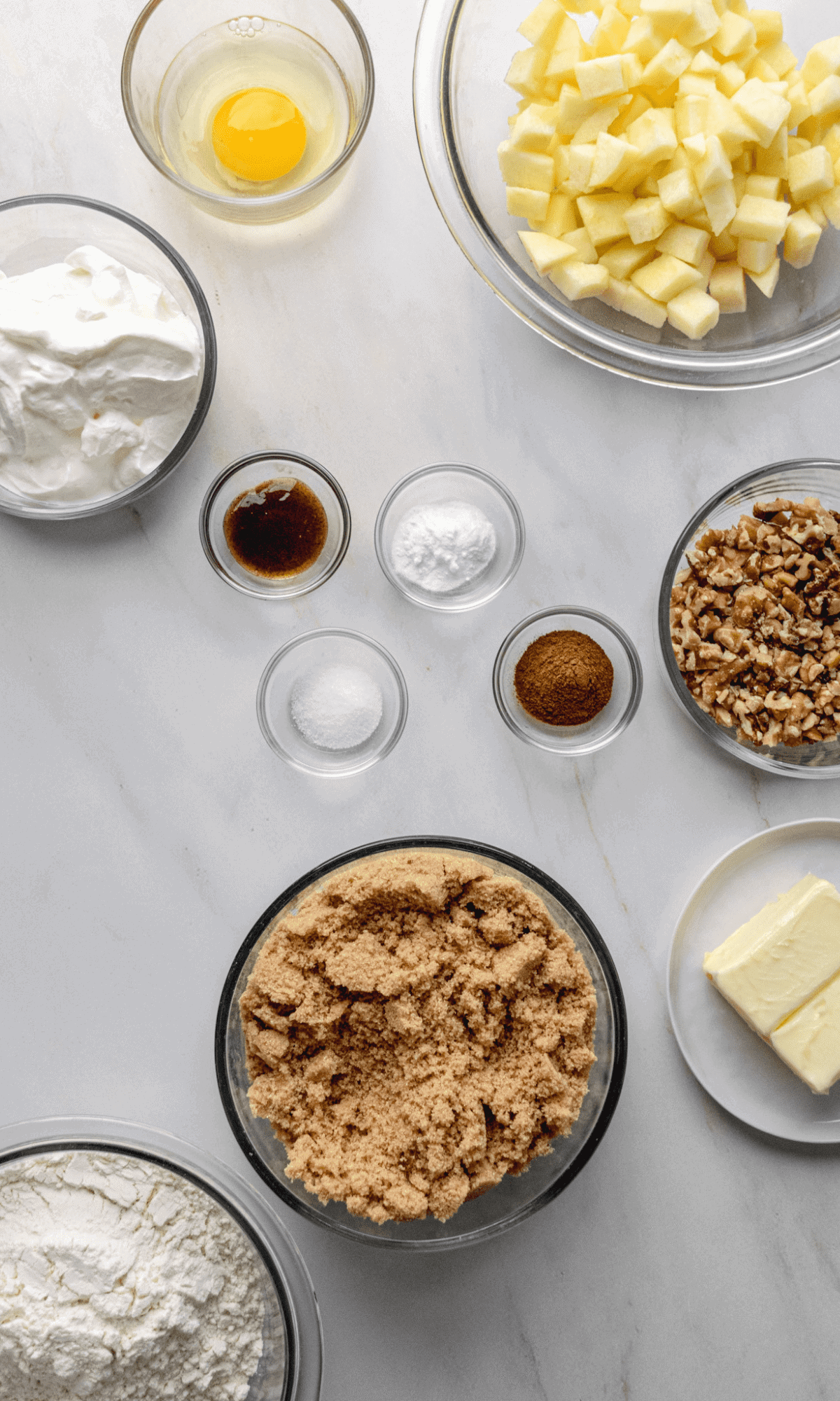 Overhead shot of ingredients for Sour Cream Apple Bars in varying bowl sizes.