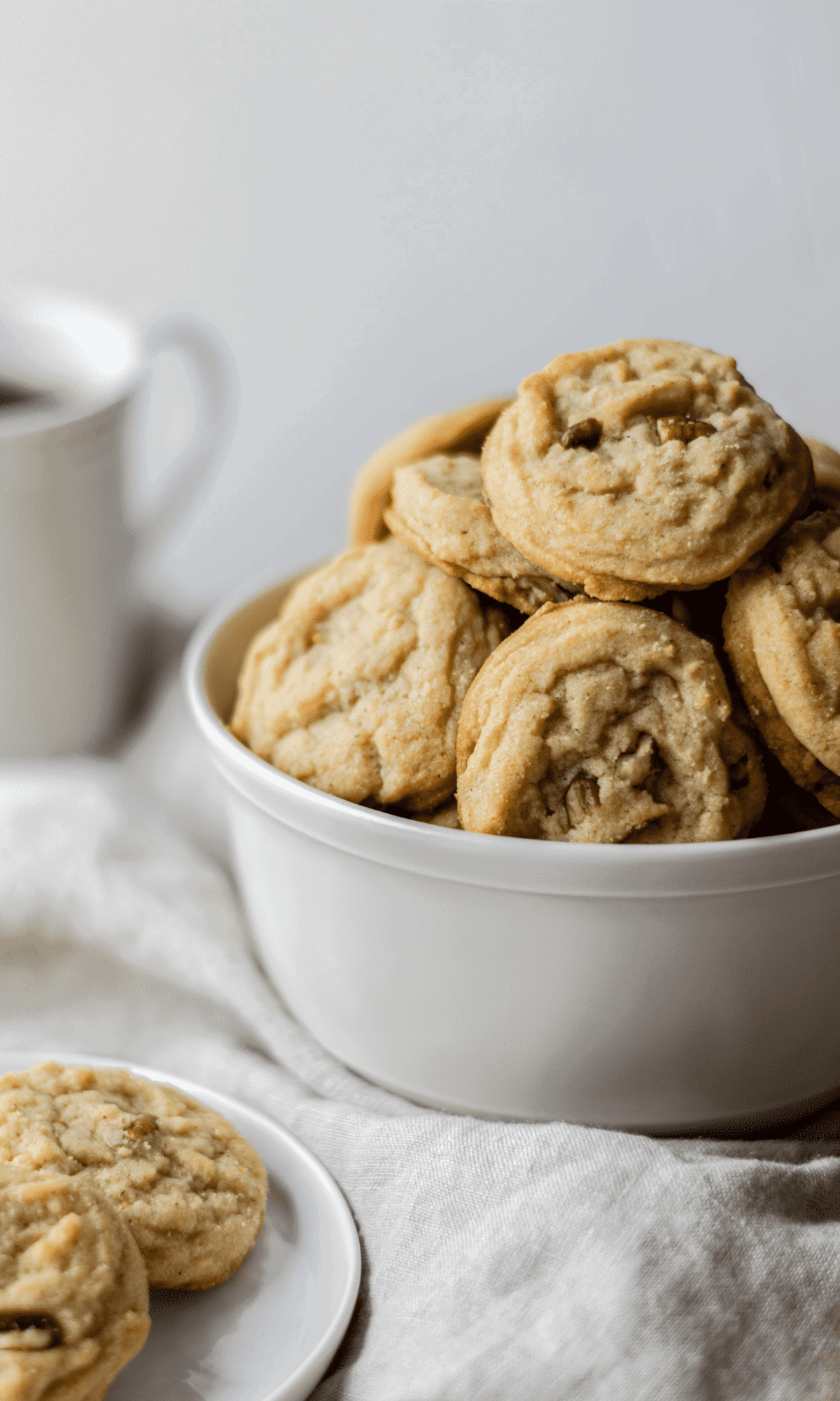 Straight on shot of Brown Butter Pecan Spice Cookies stacked in a white bowl.
