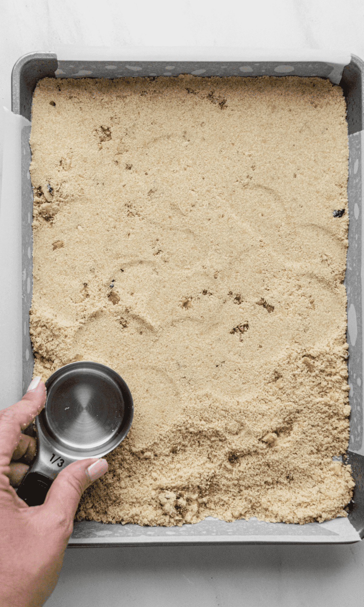 Overhead shot of crust getting pressed into baking pan using a ⅓ cup measuring cup.