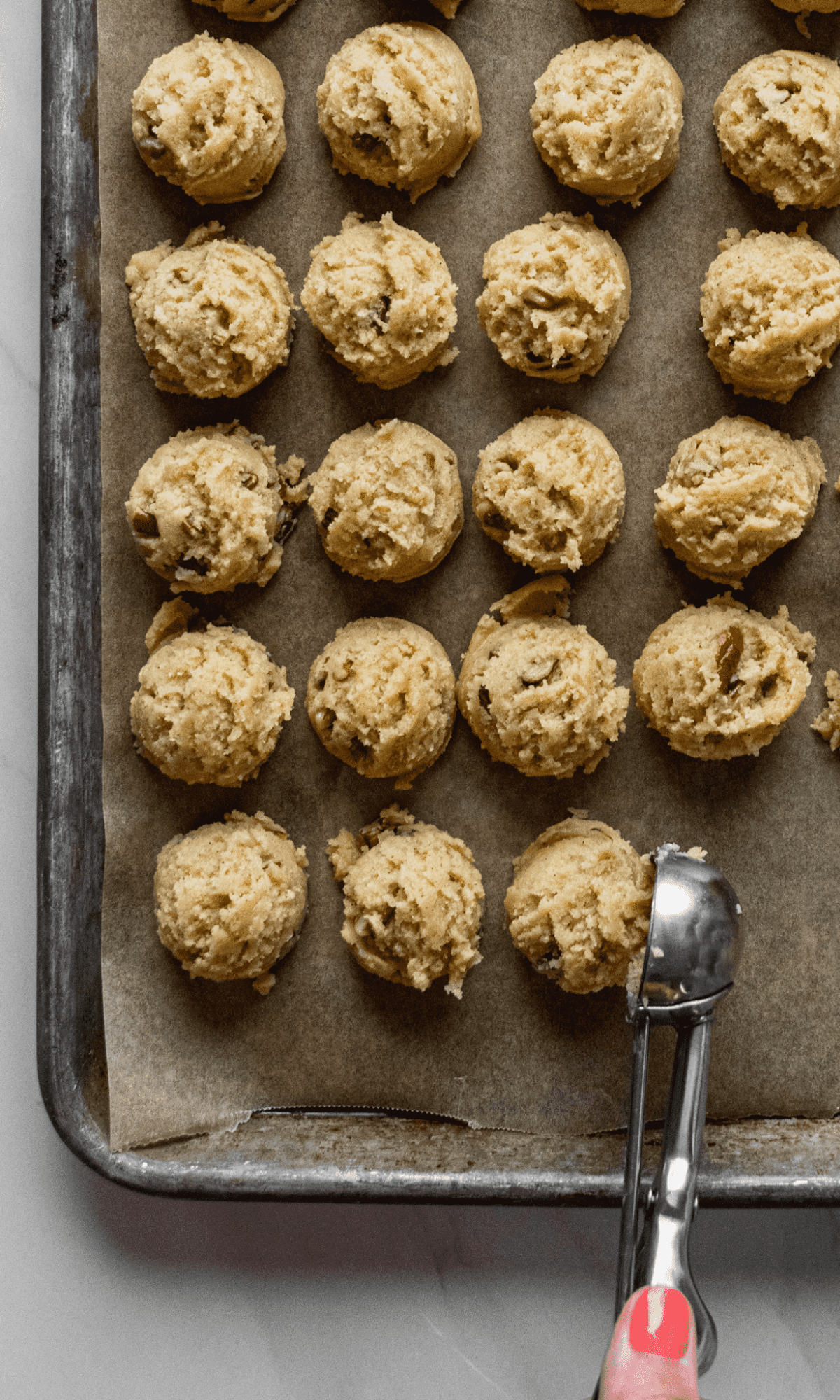 Overhead shot of scooped Brown Butter Pecan Spice Cookie dough on baking sheet lined with brown parchment paper.