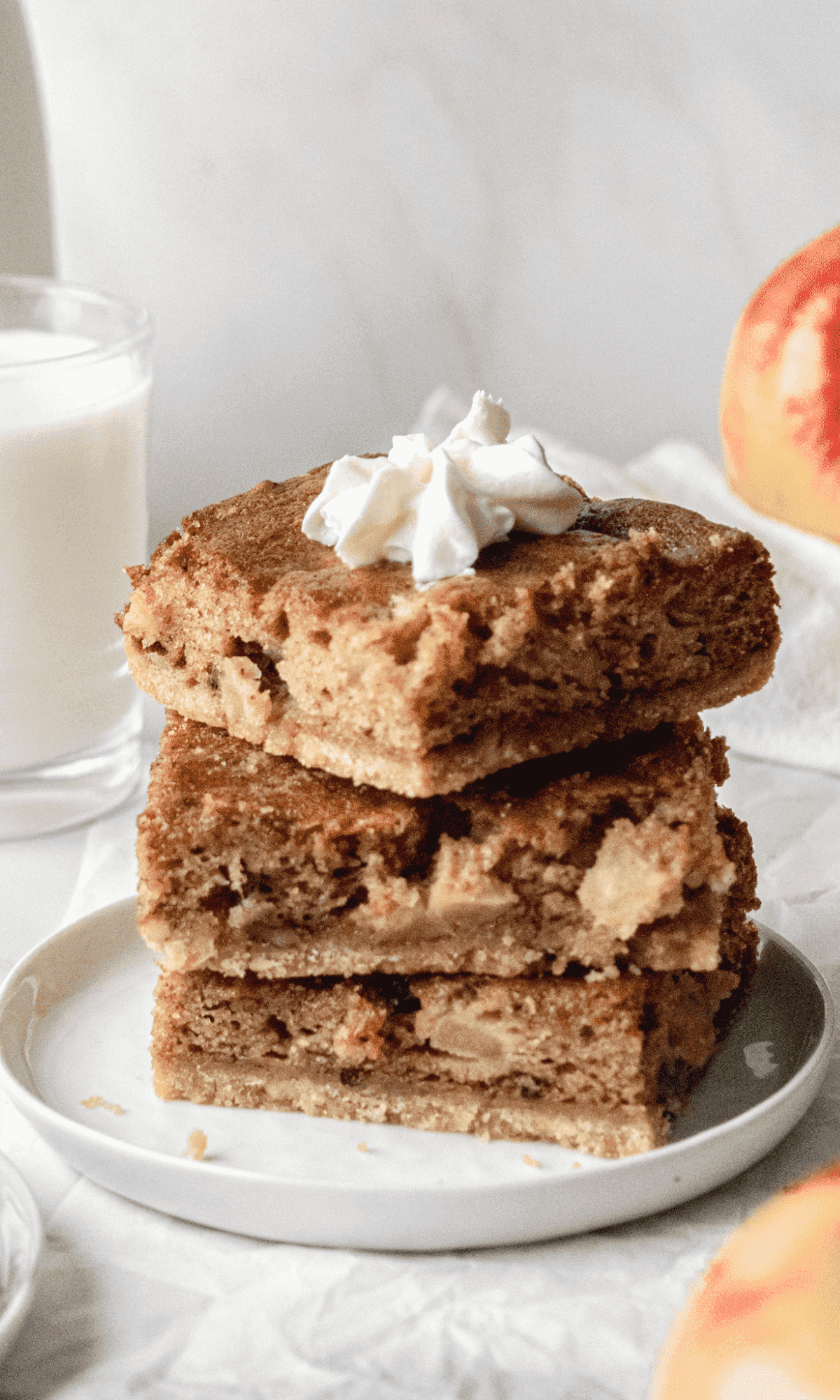 A straight-on shot of three Sour Cream Apple Bars stacked on a small white plate.