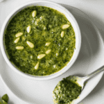 Overhead shot of a bowl of pesto in a white bowl.