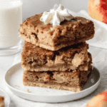 A straight on shot of three Sour Cream Apple Bars stacked on a small white plate.