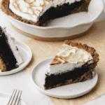 Piece of S'mores Fudge Pie on white plate with whole pie behind it.