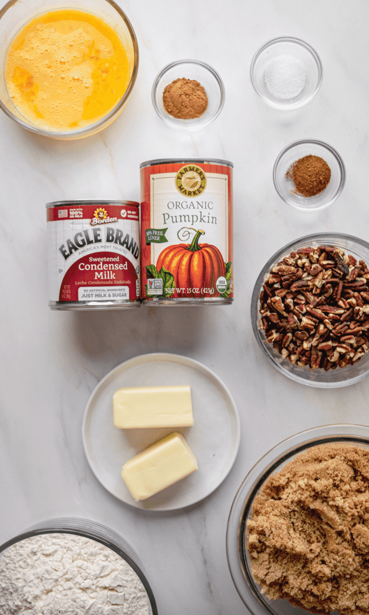 Overhead shot of ingredients for Pecan Pumpkin Pie Bars in varying bowl sizes.