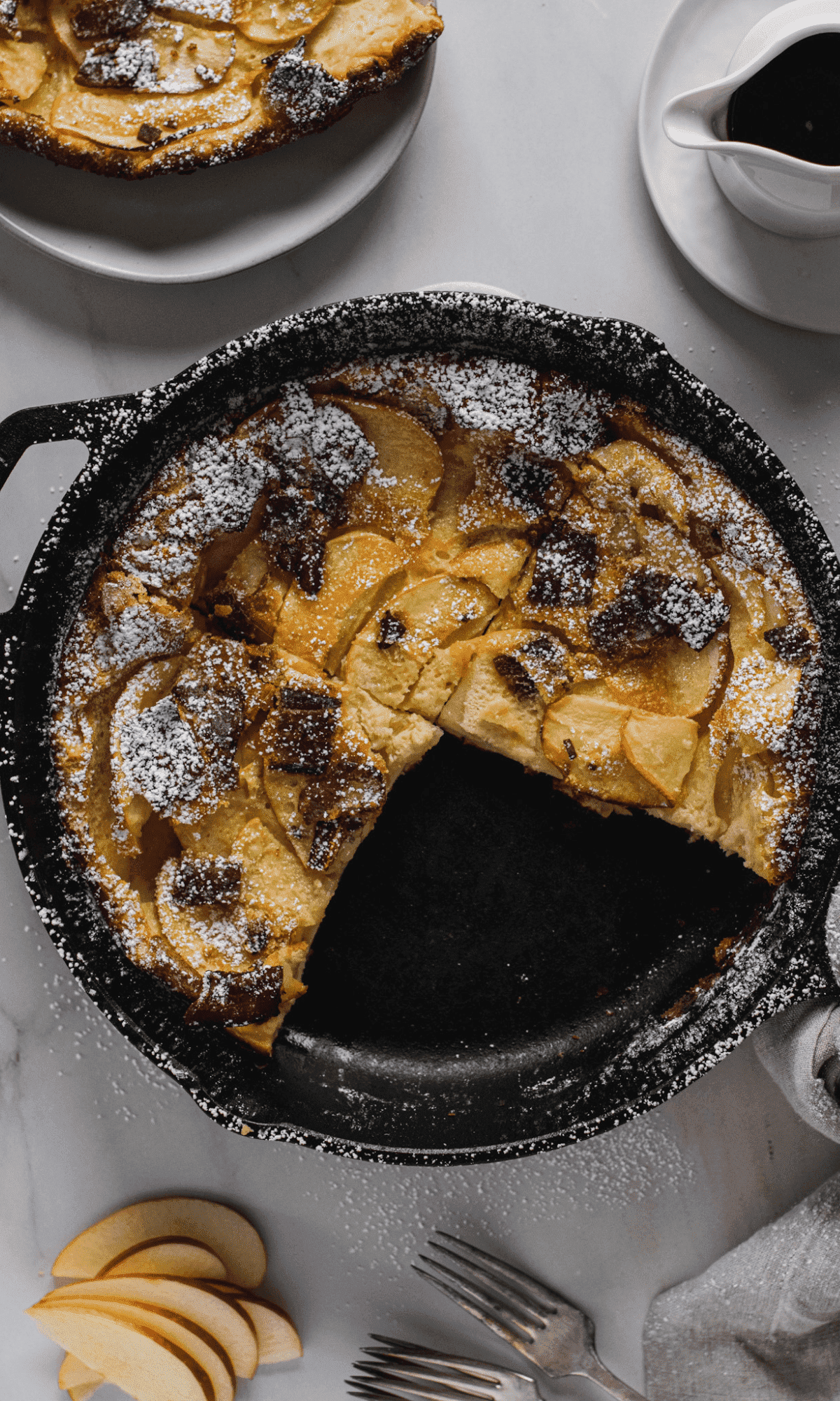 Overhead shot of Bacon Apple Dutch Baby in cast iron skillet with missing slice.