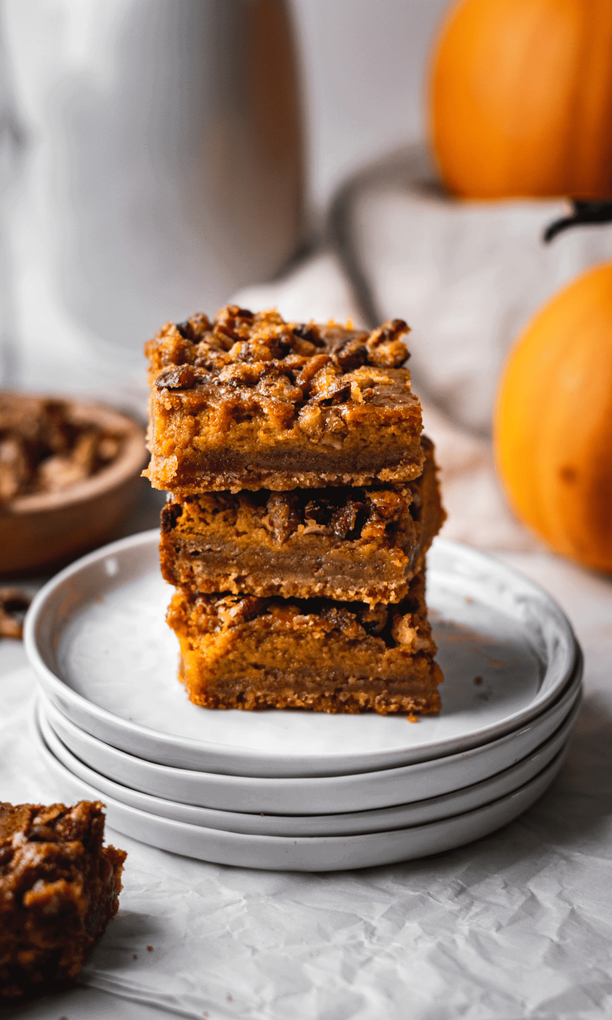 A stack of 3 Pecan Pumpkin Pie Bars on a stack of small white plates.