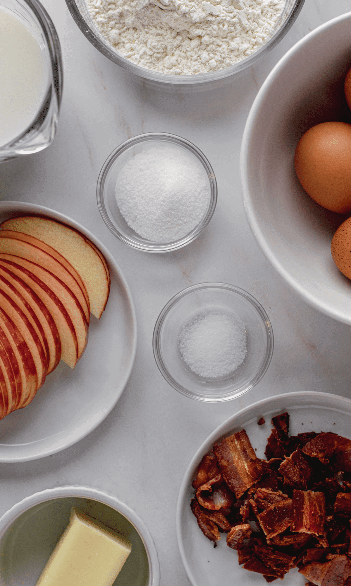 Overhead shot of ingredients for Bacon Apple Dutch Baby in varying bowl and plate sizes.