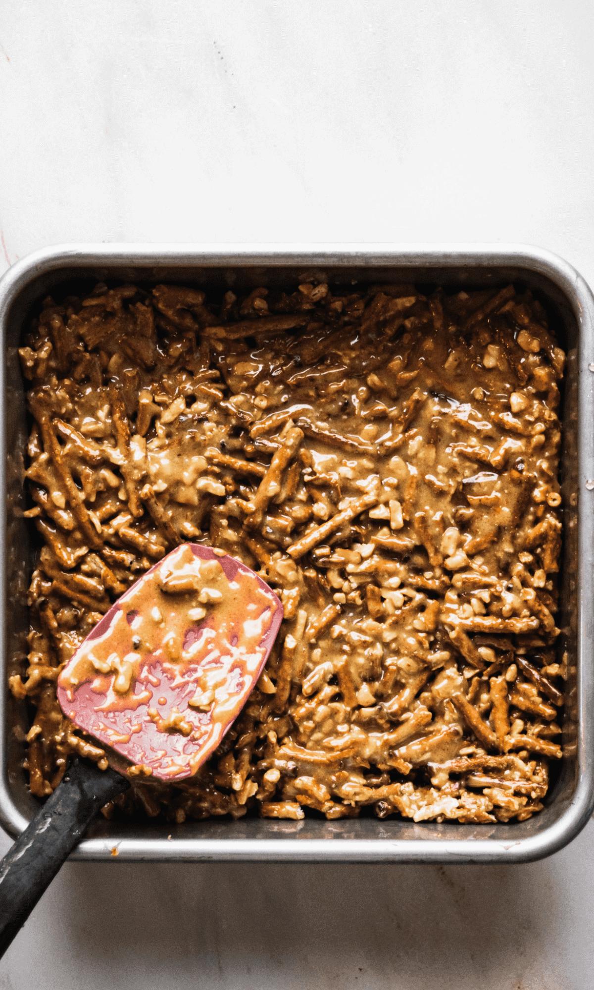 Overhead shot of pretzel, peanut butter, honey mixture for bottom layer of Salted Pretzel Scotcheroos in square cake pan.
