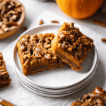 Two Pecan Pumpkin Pie Bars on a stack of small white plates.