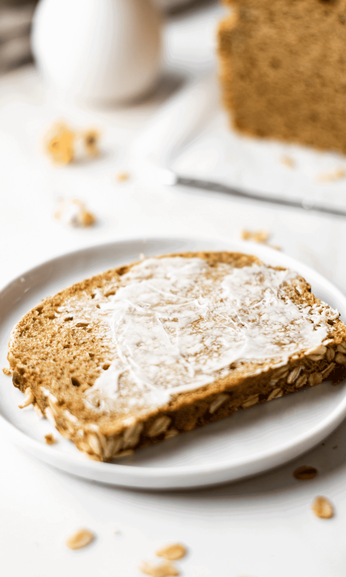 A buttered slice of Oatmeal Bread on a small white plate.