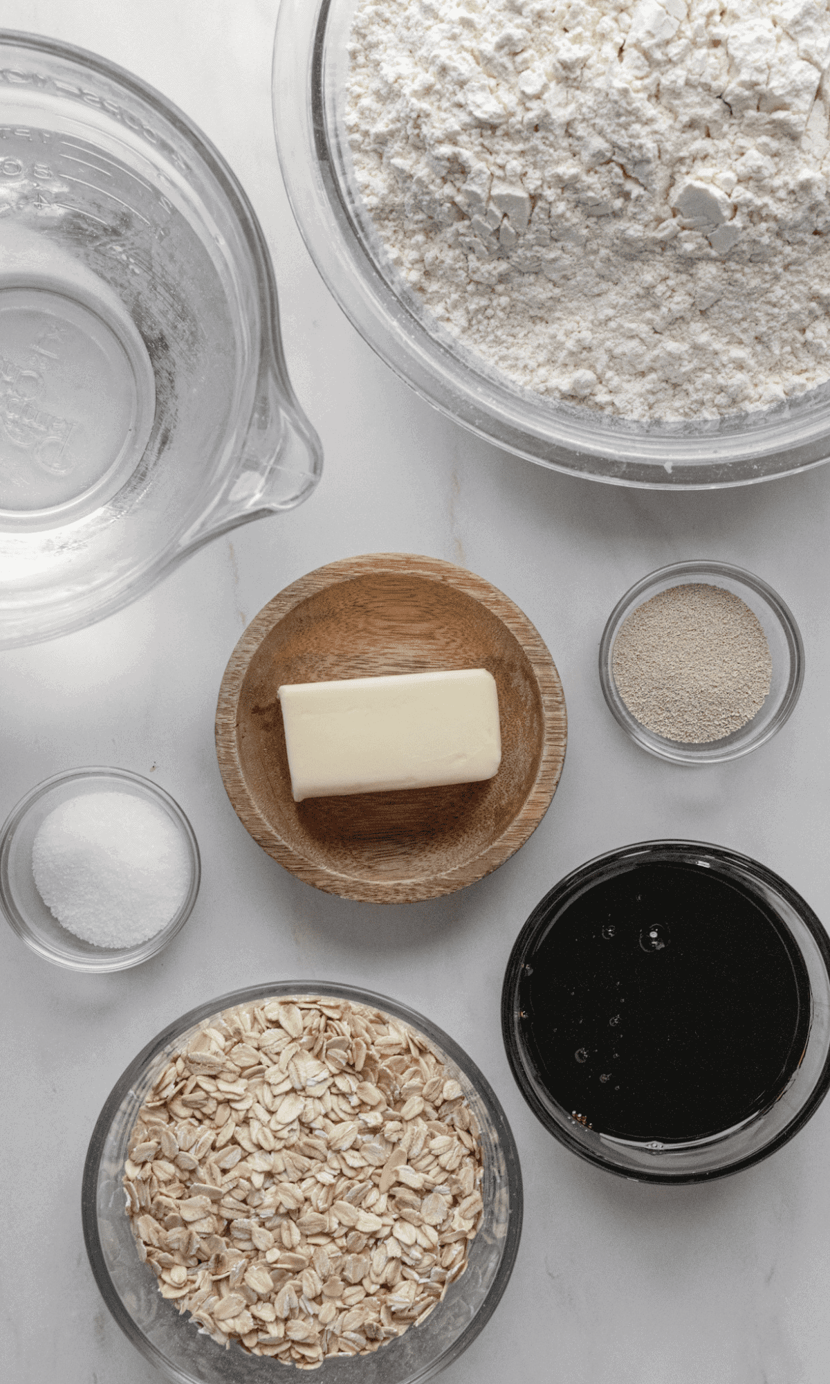 Ingredients for Oatmeal Bread in varying bowl shapes and sizers.